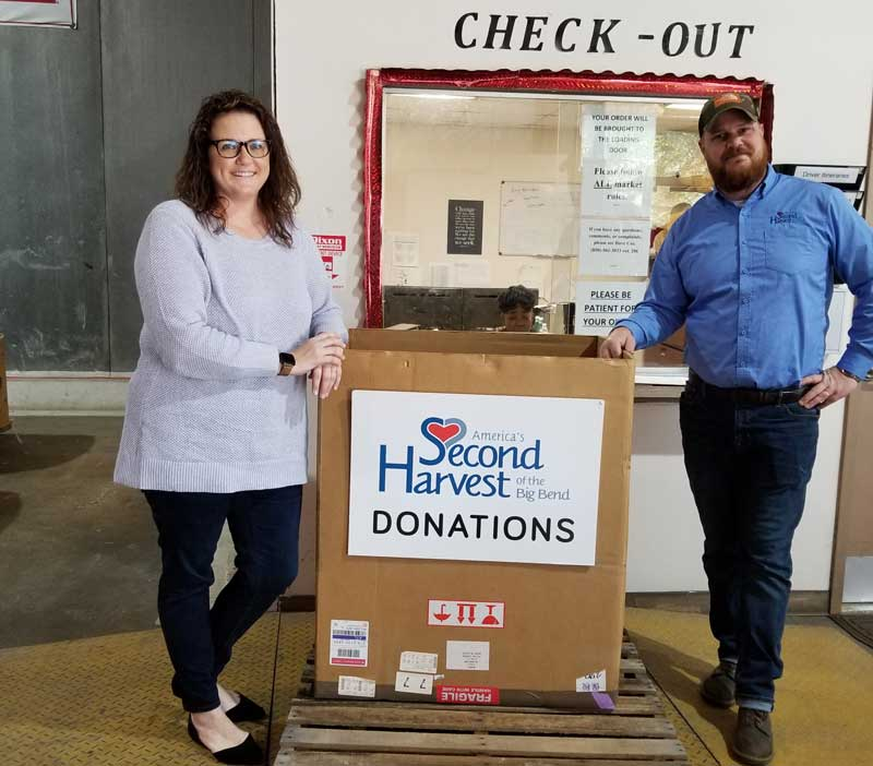 Two people standing by a Second Harvest donation box at a Farm Bureau bank