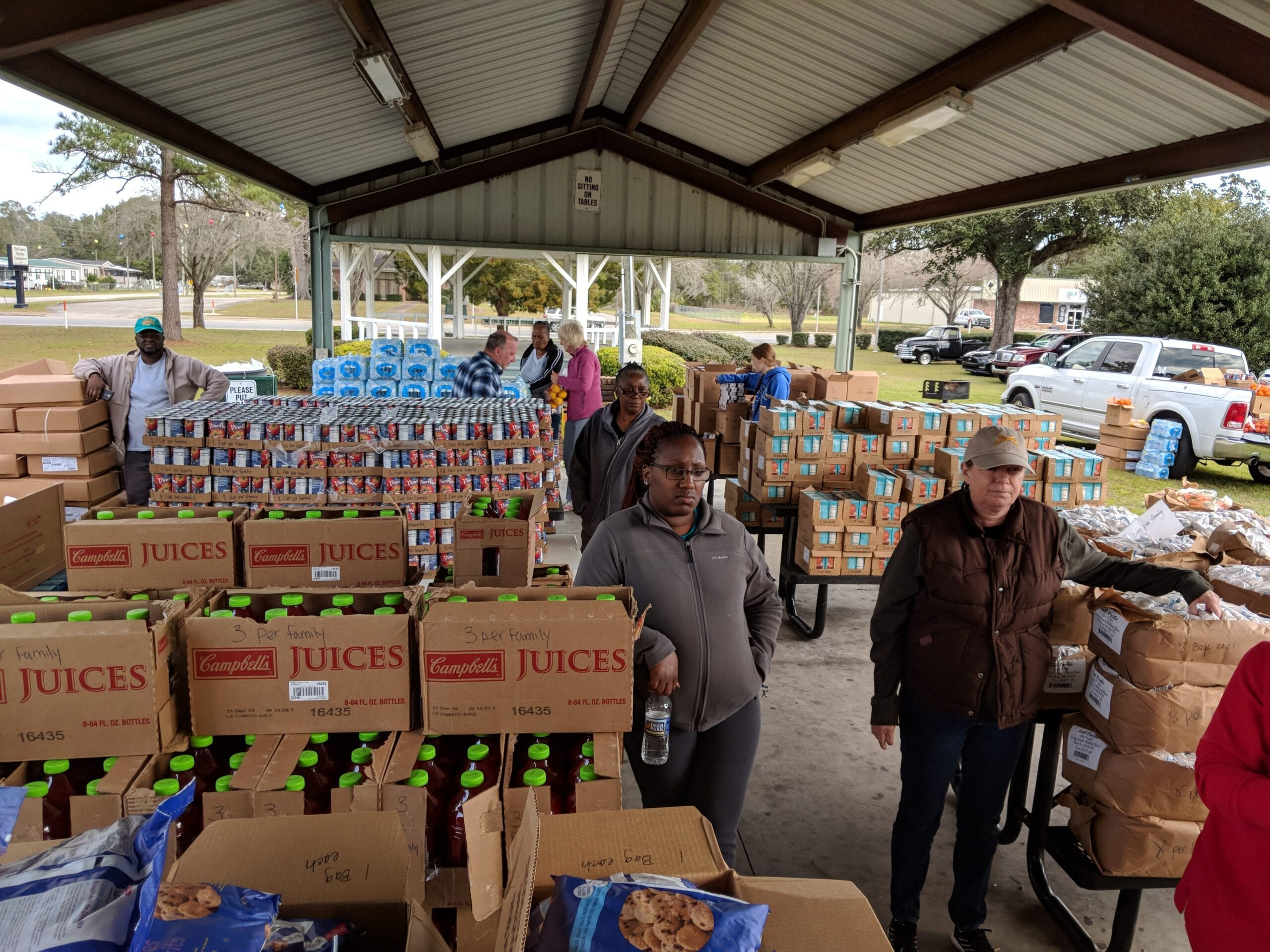 Boxes full of food and drinks stacked on tables outside at a mobile food pantry