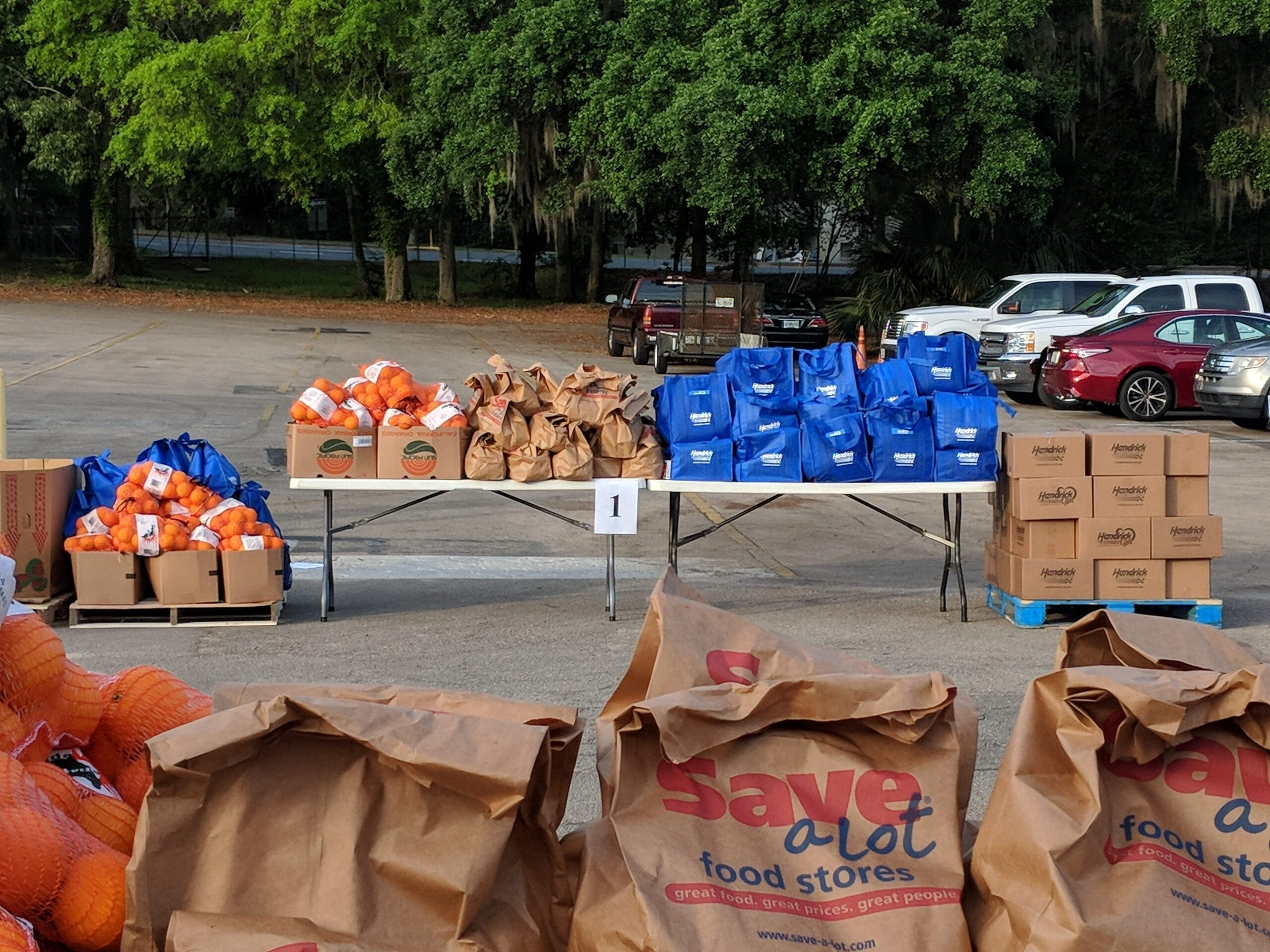 Paper bags and bxes on tables outside at a mobile food pantry